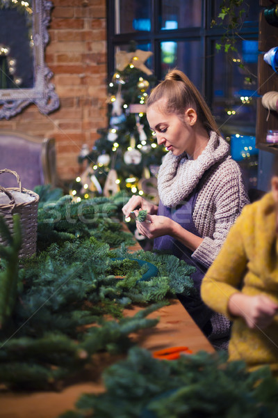 Woman with girl decorating coniferous wreath Stock photo © dashapetrenko