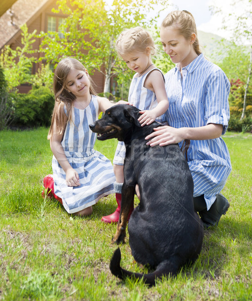 Stock photo: Happy mother with her daughters with the dog