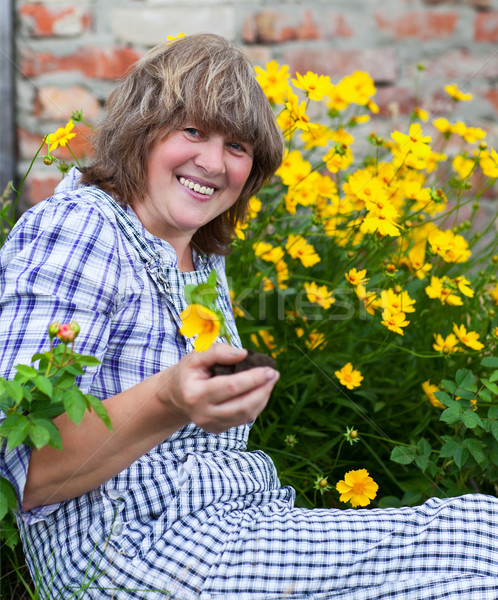 Stock photo: Happy moddle aged woman working in her backyard garden