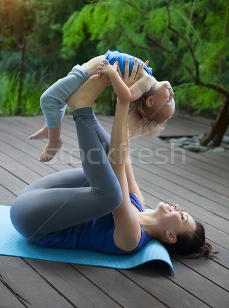 Mother and daughter doing exercise practicing yoga outdoors Stock photo © dashapetrenko