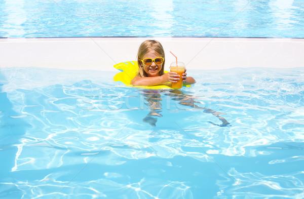 Little girl with orange juice in the pool on summer day Stock photo © dashapetrenko
