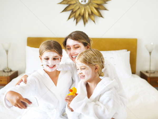 Happy mother and girls in bathrobes on bed Stock photo © dashapetrenko