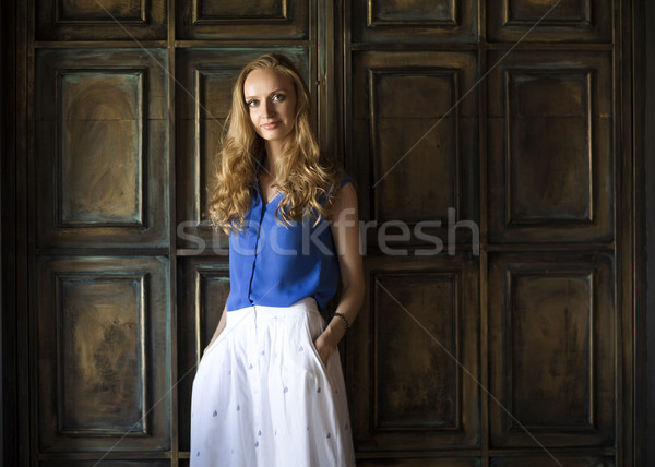 Blonde woman in blue blouse staying in front of dark wall and ke Stock photo © dashapetrenko