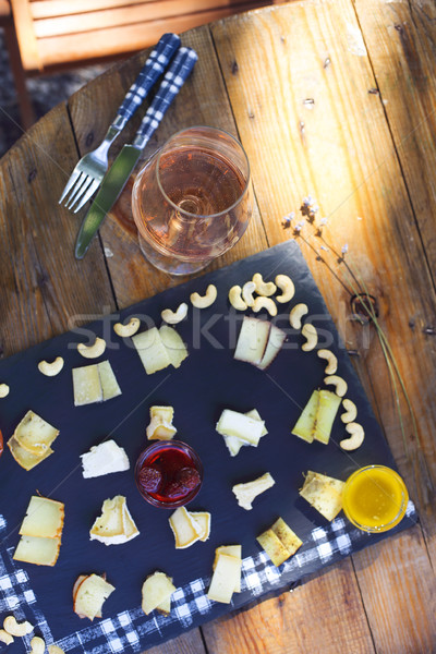 Grape, set of different kind of cheeses with a glass of pink win Stock photo © dashapetrenko