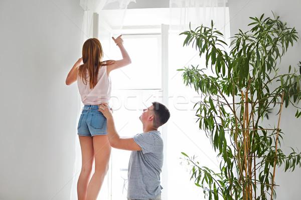 Heureux couple fenêtre ouverture rideaux nouvelle maison Photo stock © dashapetrenko