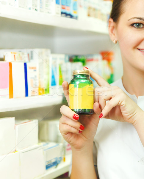Closeup of a blurred female pharmacist holding out tablets in bo Stock photo © dashapetrenko