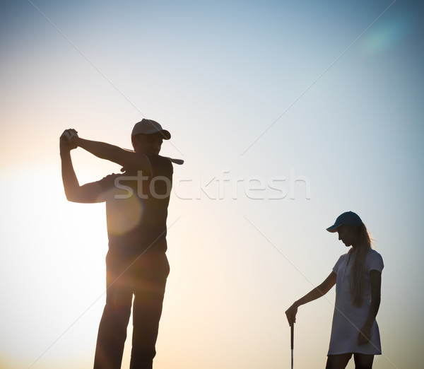 Male and female golfers at sunset Stock photo © dashapetrenko