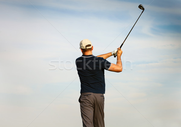 Stock photo: Athletic young man playing golf, golfer hitting fairway shot