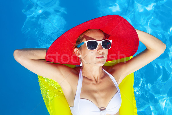 Woman with perfect tanned body lying on yellow air mattress in t Stock photo © dashapetrenko
