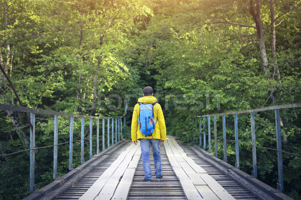 Tourist man walking across wooden bridge  Stock photo © dashapetrenko