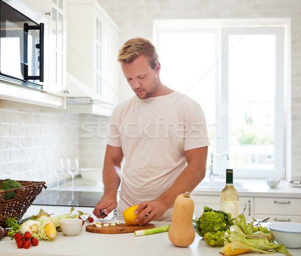 Handsome man cooking at home preparing salad in kitchen Stock photo © dashapetrenko