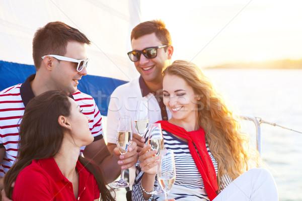Uśmiechnięty znajomych posiedzenia jacht pokład powitanie Zdjęcia stock © dashapetrenko