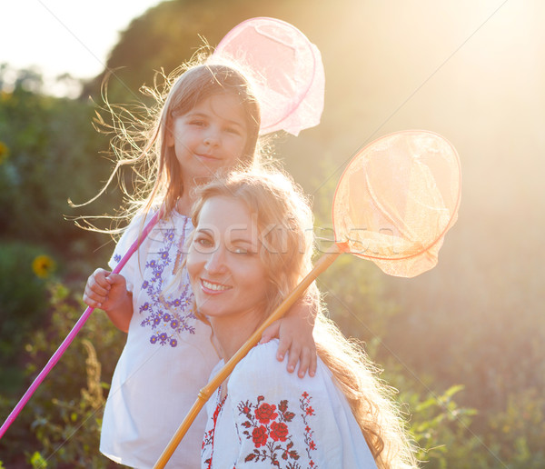 Cheerful mother and her daughter playing in a field with insect  Stock photo © dashapetrenko
