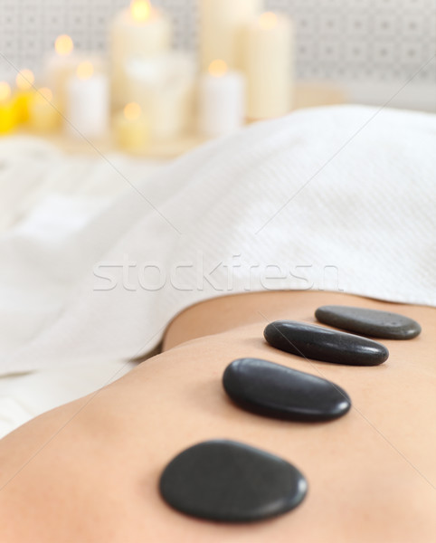 Closeup of young woman receiving hot stone massage Stock photo © dashapetrenko