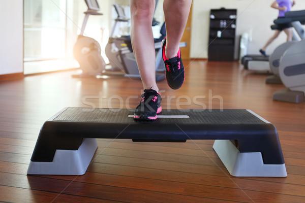 Woman doing step aerobics while in health club Stock photo © dashapetrenko