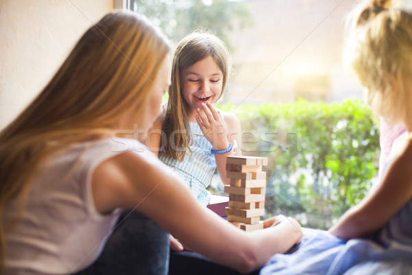 Happy mother with two children playing the wooden blocks tower Stock photo © dashapetrenko