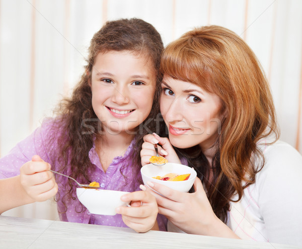 Mother and daughter eating cereal and fruit Stock photo © dashapetrenko