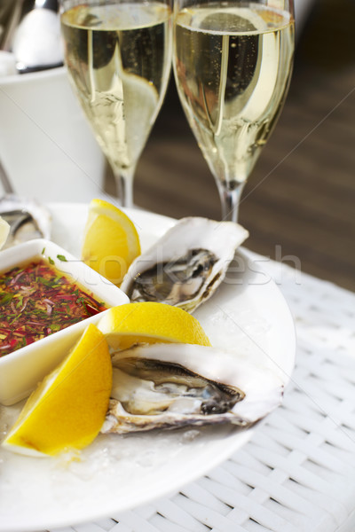 Fresh oysters shell with lemon and glasses of champagne. Top of  Stock photo © dashapetrenko