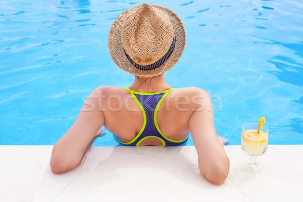 Stock photo: Pretty brunette woman enjoying lemonade in a swimming pool