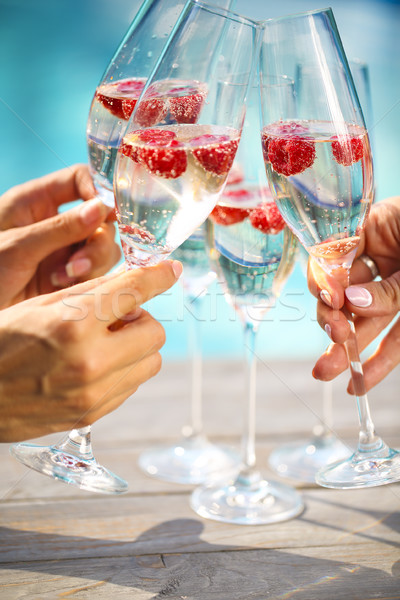 Hands with Champagne glasses with raspberry Stock photo © dashapetrenko