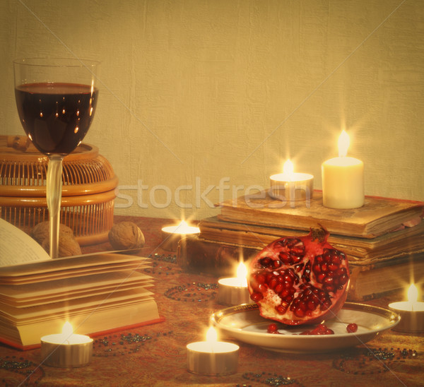 Still life with pomegranate, red wine, books and candles Stock photo © dashapetrenko