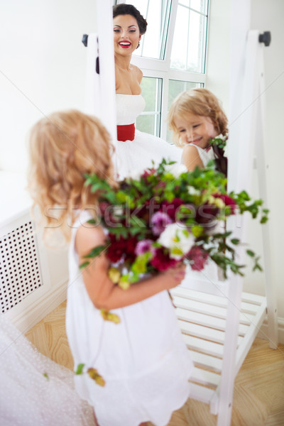 Smiling happy bride and a flower girl indoors Stock photo © dashapetrenko