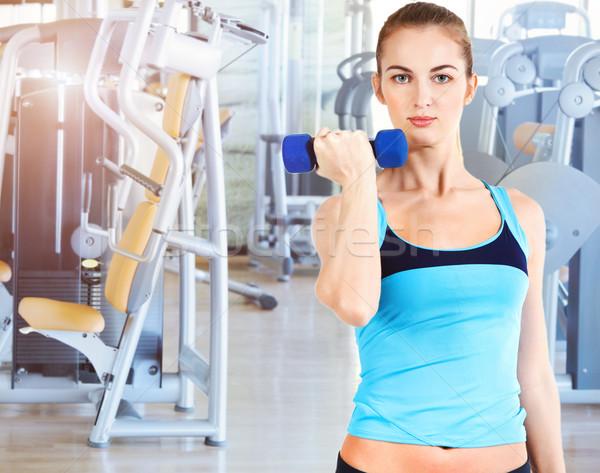 Sporty female doing physical exercise in gym Stock photo © dashapetrenko