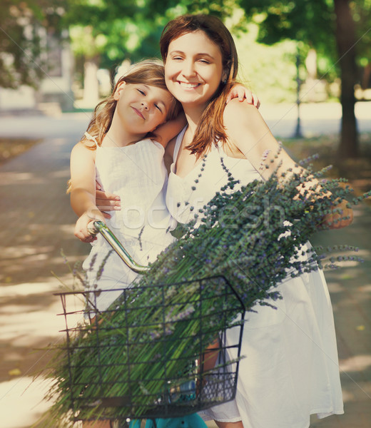 Beautiful and happy young woman on bicycle with her daughter Stock photo © dashapetrenko