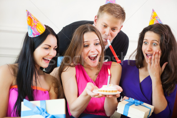 Girl looking at birthday cake surrounded by friends at party Stock photo © dashapetrenko
