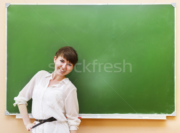 Student girl standing near clean blackboard in the classroom Stock photo © dashapetrenko