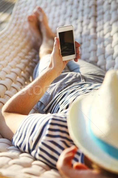 Férfi kalap függőágy mobiltelefon nyár nap Stock fotó © dashapetrenko