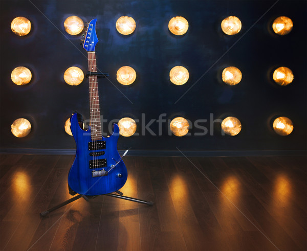 Music concept. Electric guitar standing on the wooden floor near Stock photo © dashapetrenko