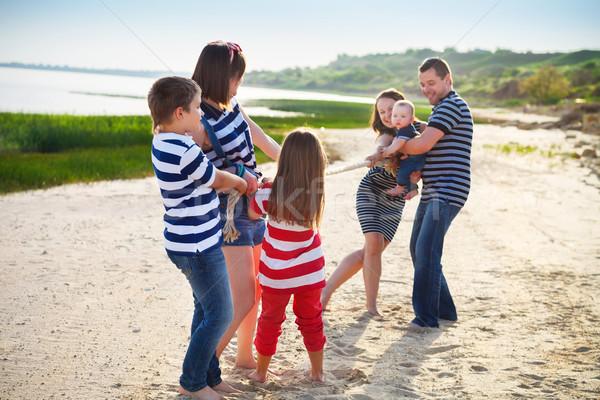 Tug of war - family playing on the beach Stock photo © dashapetrenko