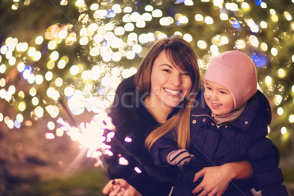 Mother and little daughter with Bengal light over Christmas back Stock photo © dashapetrenko