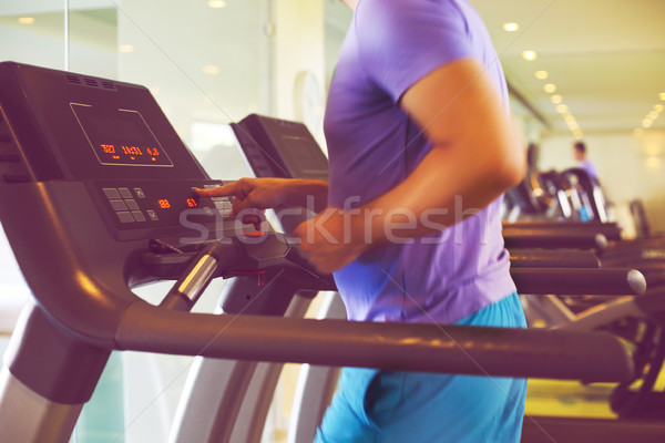 Healthy young man training on a treadmill in a sport center Stock photo © dashapetrenko