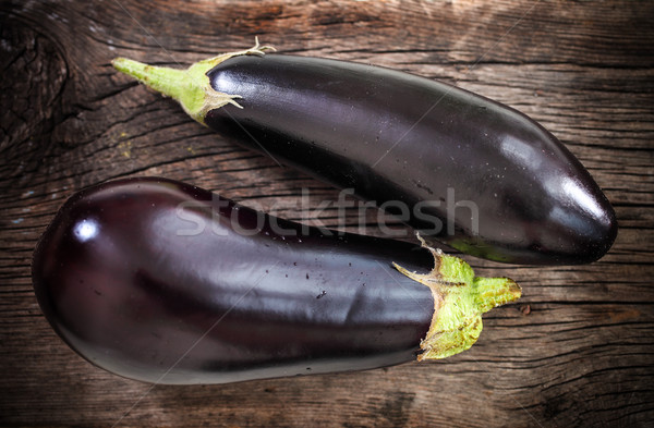 Fresh eggplants with leaves over dark background Stock photo © dashapetrenko