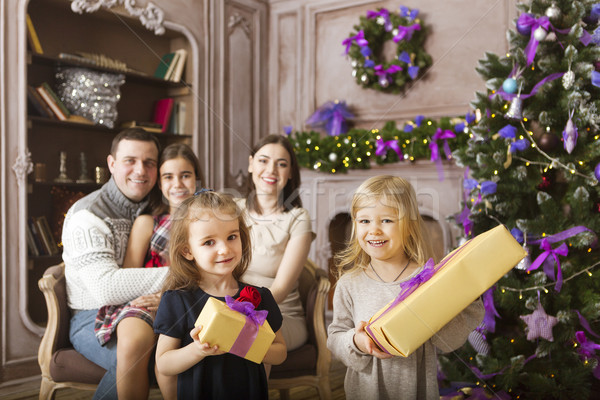 Stock photo: Stylish family celebrating christmas in room over christmas tree