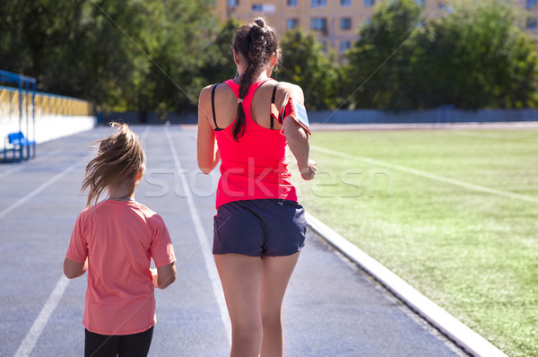 Mother and little daughter are doing exercise in the stadium Stock photo © dashapetrenko