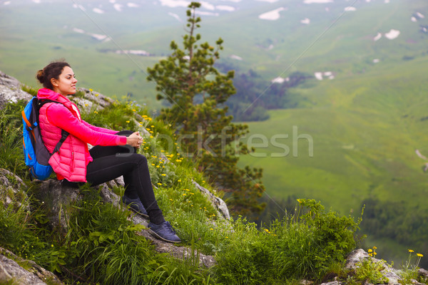 Hiker with backpack relaxing on top of a mountain and enjoying v Stock photo © dashapetrenko