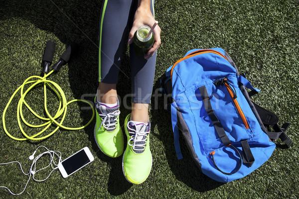 Sporty woman holding green juice sitting on grass Stock photo © dashapetrenko