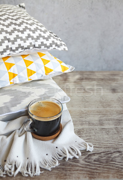 Yellow and grey pillows and cup of coffee on the wall background Stock photo © dashapetrenko