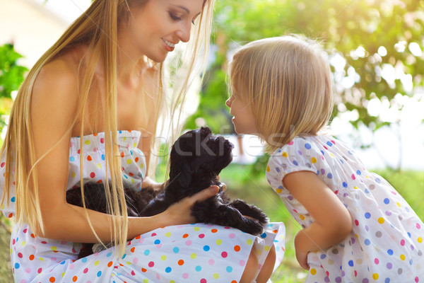 Cute little girl and her mother hugging dog puppies Stock photo © dashapetrenko
