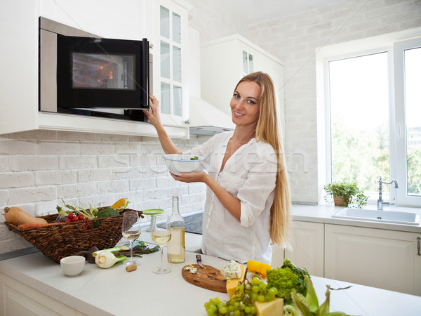 Young smiling woman cooking at the kitchen Stock photo © dashapetrenko