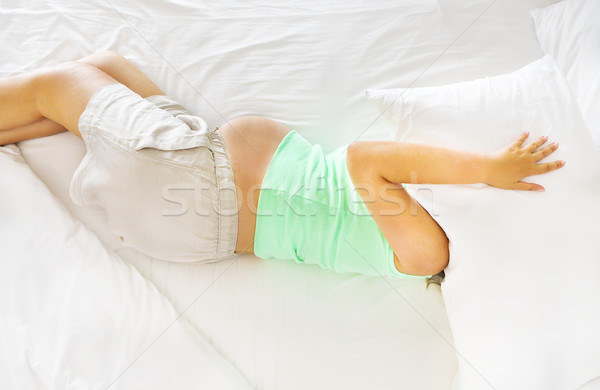Young pregnanat woman in the bed with face under pillow Stock photo © dashapetrenko