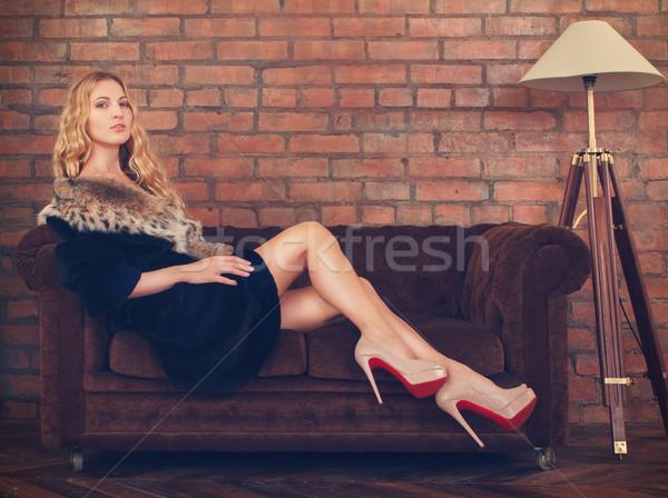 красивая женщина шуба сидят диван портрет стены Сток-фото © dashapetrenko