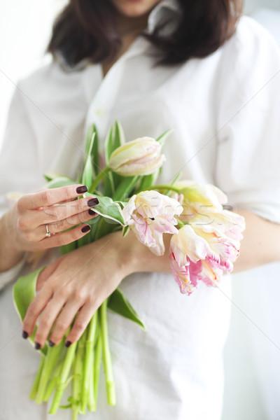 Beautiful young woman holding a bunch of delicate spring pink tu Stock photo © dashapetrenko