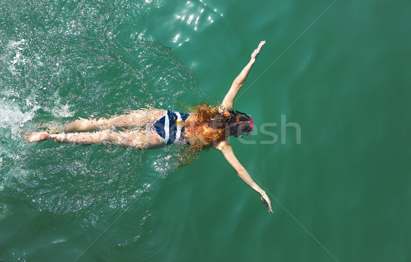 Aerial top down view of a girl wearing swimming mask in the sea  Stock photo © dashapetrenko