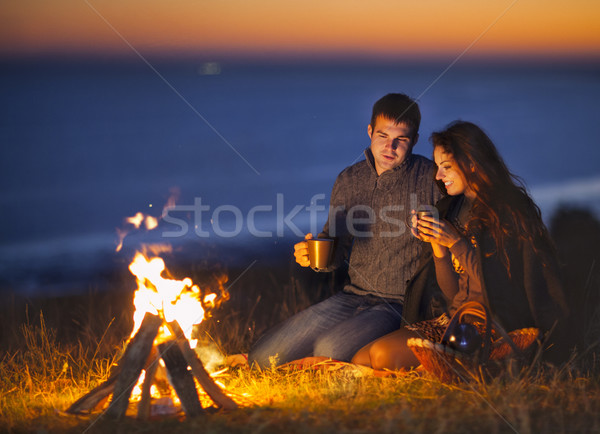 Portrait of the happy couple sitting by fire on autumn beach  Stock photo © dashapetrenko