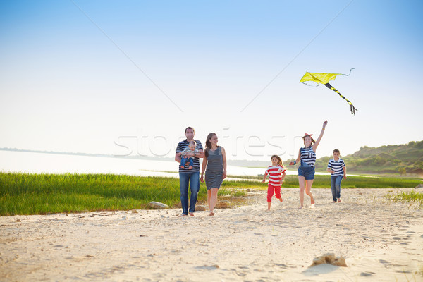 Happy young family with flying a kite on the beach Stock photo © dashapetrenko