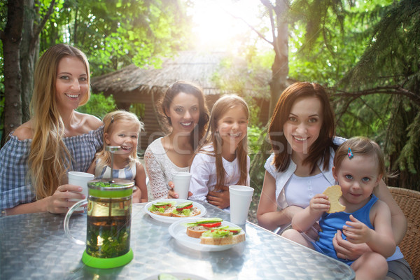 Happy mothers and her adorable little daughters at outdoors cafe Stock photo © dashapetrenko